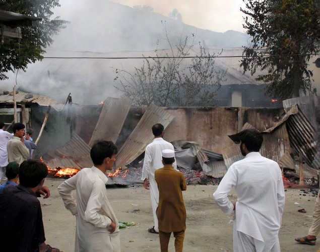 Pakistani local residents look at the burning government offices following a protest rally organized by Pakistani Muslims against an anti-Islam movie in the northwestern town of Warai, in Upper Dir district.