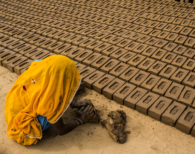 A woman shapes a mud-based mixture into bricks at a brick making facility on May 23, 2012 in a village near Jaipur, India.