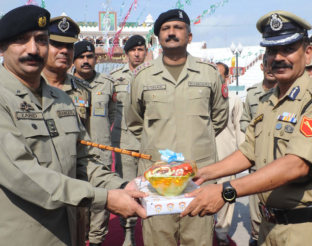 Indian Border Security Force (BSF) Inspector General (IG) Aditya Mishra (R) and BSF Commander Sumer Singh (2L) presents sweets to Pakistani Ranger Sector Commander brigadier Zahid Rana (L) during a flag hoisting ceremony to celebrate India's Independence Day at the India-Pakistan Wagah border post on August 15, 2012.