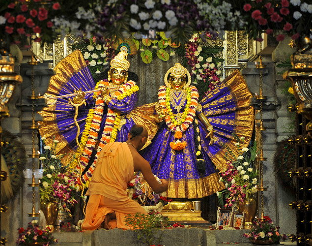 An Indian Hindu priest preforms rituals on the Hindu God Lord Krishna (L) and his consort Radha at the International Society for Krishna Consciousness (ISKCON) temple in Bangalore on August 9, 2012 on the eve of 'Krishna Janmashtami'.