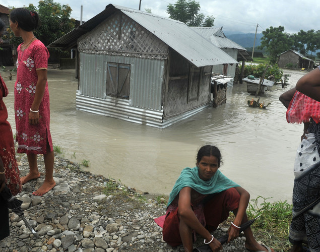 Indian villagers sit near their houses surrounded by flood waters at Milanmore village on the outskirts of Siliguri.