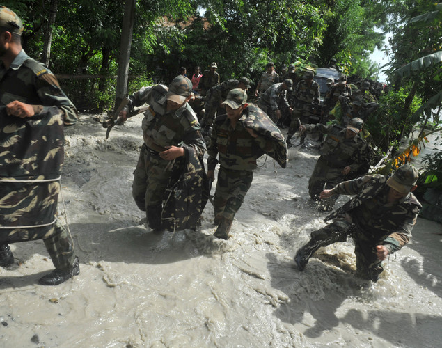 Indian army personal wade through flood waters at Milanmore village on the outskirts of Siliguri.