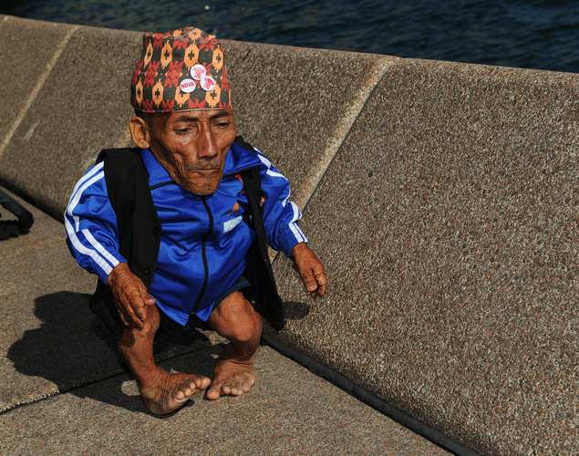 Chandra Bahadur Dangi (R), the 72-year-old Nepali crowned the 'world's shortest man' by Guinness World Records, walks along a wall to attend a press conference at Circular Quay on Sydney Harbor at the start of a week of promotional engagements.