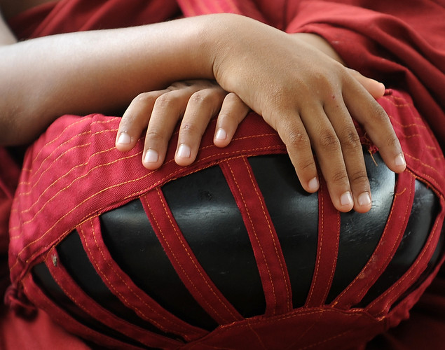 A young Sri Lankan Buddhist monk holds a vessel for alms during the annual Buddhist festival of Vesakha in Colombo.