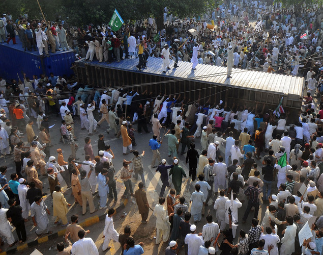 Pakistani Muslim demonstrators topple a freight container, placed by police to block a street, during a protest against an anti-Islam film in Lahore.