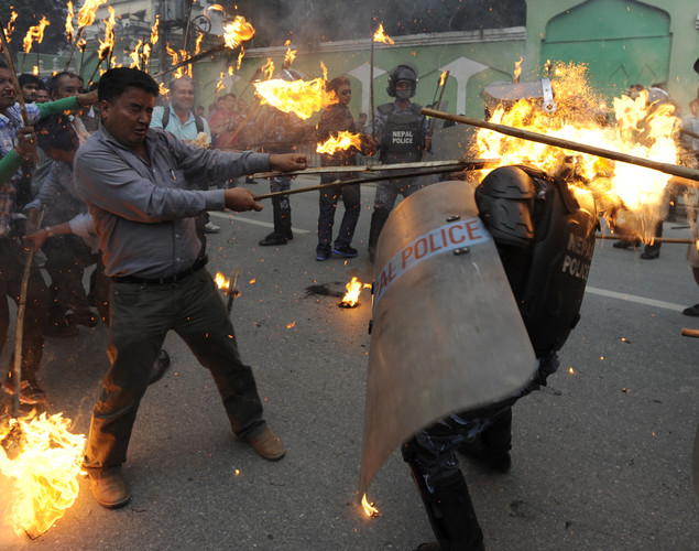 A Nepalese riot policeman (R) is hit by a flaming torch during clashes with Youth Force Wing activists of the Communist Party of Nepal (UML) during a protest demanding the resignation of Prime Minister Baburam Bhattarai in Kathmandu.