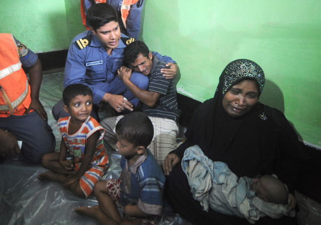 A Rohingya Muslim woman from Myanmar holding her six day old baby and her family, who tried to cross the Naf river into Bangladesh to escape sectarian violence, cry in a Bangladeshi Coast guard station in Teknaf on June 19, 2012, before being sent back to Myanmar.