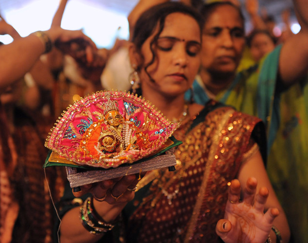An Indian devotee, holding an idol of Radha and Krishna, dances during a religious function organized by Indian yoga Guru Baba Ramdev (unseen) in Ahmedabad.