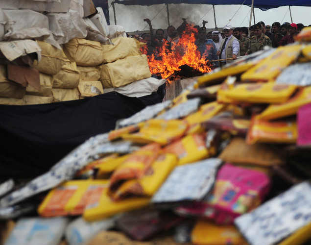 Pakistani officials torch a pile of seized drugs during a ceremony to mark International Day against Drug Abuse and Illicit Trafficking, in Karachi.