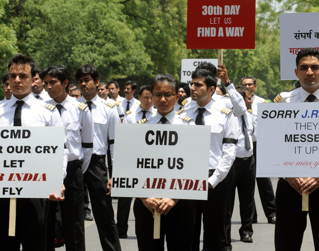 Striking Air India pilots hold placards during a protest march in New Delhi.