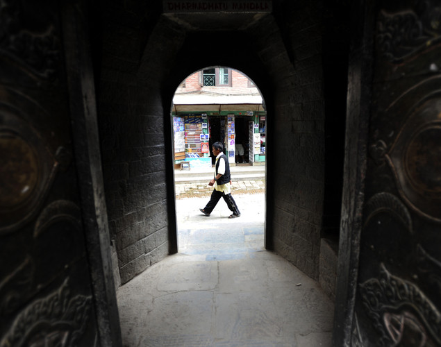 A Nepalese man walks past the Golden Temple near Patan Durbar Square in Lalitpur, about five kms southeast of Kathmandu on August 30, 2012. The Golden Temple was founded during the 12th Century near Patan Durbar Square, a UNESCO World Heritage Site, famous for fine ancient art, making of metallic and stone carving statues.