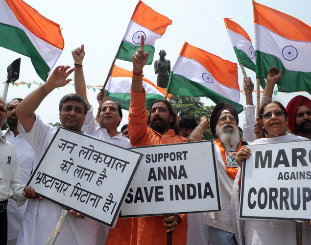 Supporters of anti-corruption activist Anna Hazare hold national flags and placards as they shout slogans during a protest in Amritsar.
