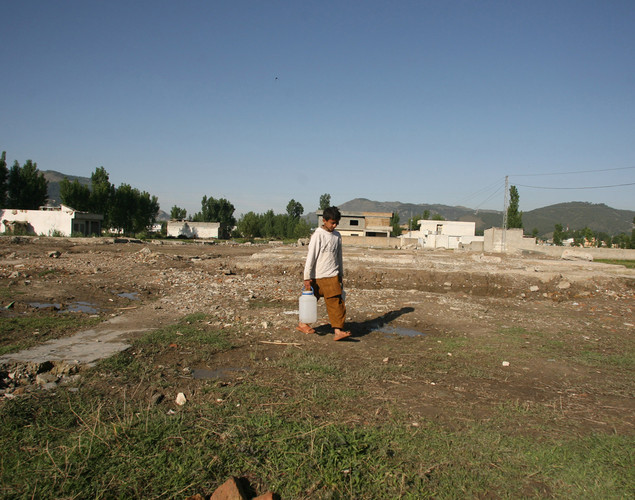 A Pakistani boy carries water cans at the site of the demolished compound of slain Al-Qaeda leader Osama bin Laden in northern Abbottabad.