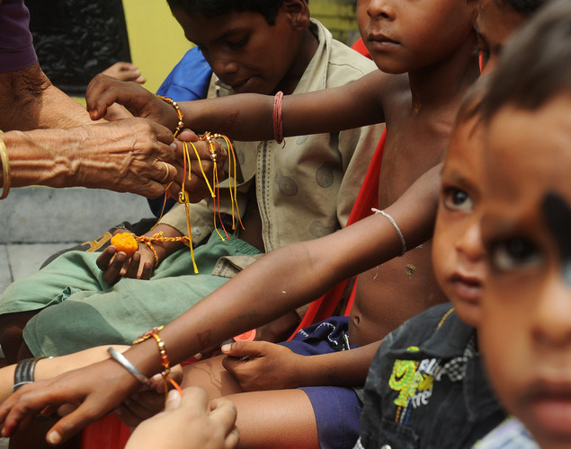 An Indian member of a voluntary organization ties a rakhi bracelet around the wrists of street children in Kolkata.