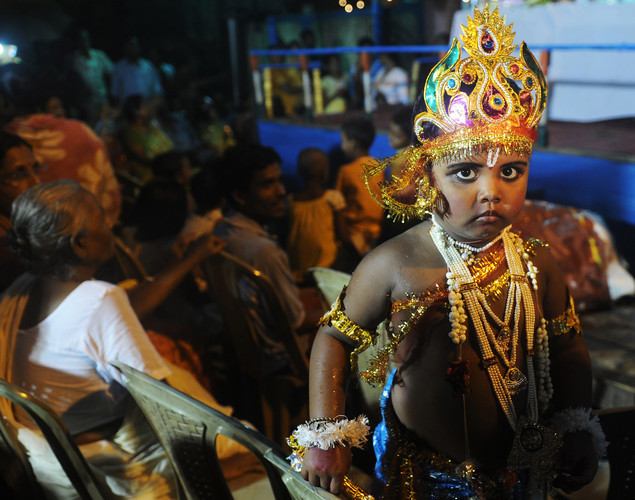 A young Indian Hindu devotee dressed as the Hindu God Lord Krishna stands amidst his family members before a fancy dress competition held at a local temple in Kolkata on August 9, 2012 on the eve of 'Krishna Janmashtami'.
