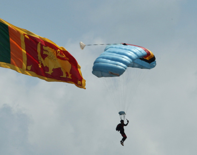 A Sri Lankan military officer parachutes next to national flag during military parade rehearsals in preparation for the celebration of the third anniversary of the end of the civil war and the defeat of the separatist Tamil Tiger rebels.