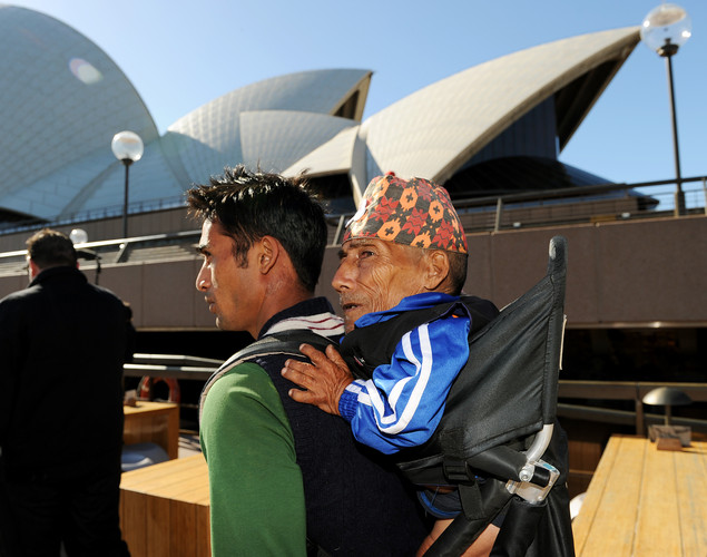 Chandra Bahadur Dangi (R), the 72-year-old Nepali crowned the 'world's shortest man' by Guinness World Records, is carried by his nephew Dolakh Dangi past the Sydney Opera House at the start of a week of promotional engagements.