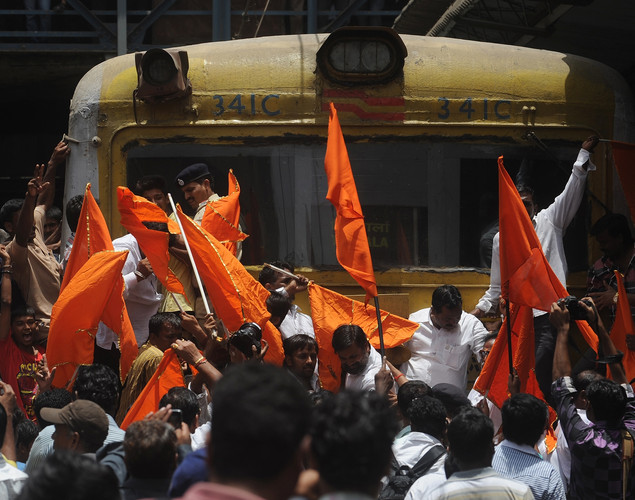 Indian Shiv Sena party workers wave flags as they climb onto a railway engine during a nationwide strike in Mumbai.