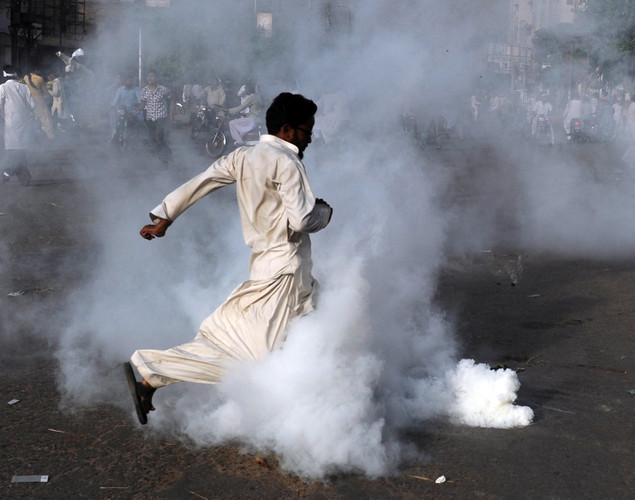 A Pakistani Muslim demonstrator kicks a tear gas shell during a protest against an anti-Islam film in Karachi.
