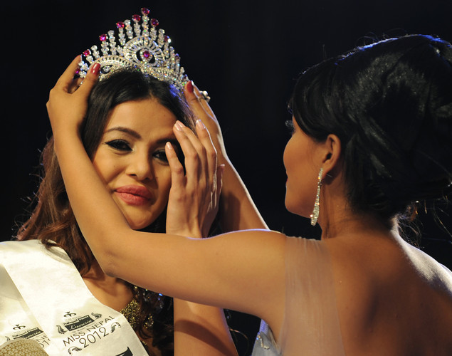 Newly-crowned Miss Nepal Shristi Shrestha (L) has her crown fitted by former Miss Nepal Malina Joshi (R), following the contest in Kathmandu.