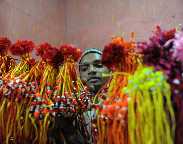An Indian Muslim arranges prepared Rakhis for the forthcoming Hindu festival of Raksha Bandhan at his cottage industry in Millatnagar area of Ahmedabad.