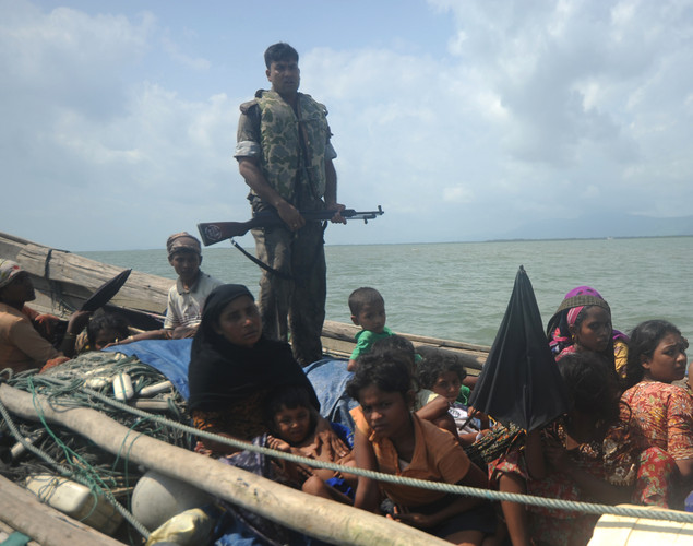 A Bangladeshi border guard stands on an intercepted boat carrying Rohingya Muslims trying to cross the Naf river into Bangladesh to escape sectarian violence, in Teknaf.