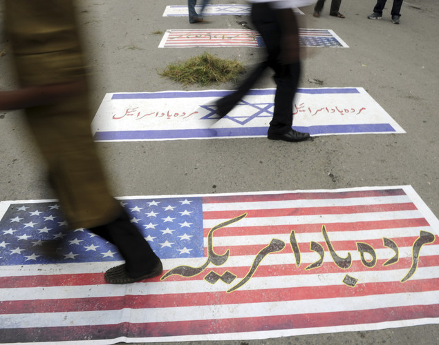 Pakistani Muslim demonstrators walk over US and Israeli flags as they attempt to reach the US embassy during a demonstration against an anti-Islam film in Islamabad.