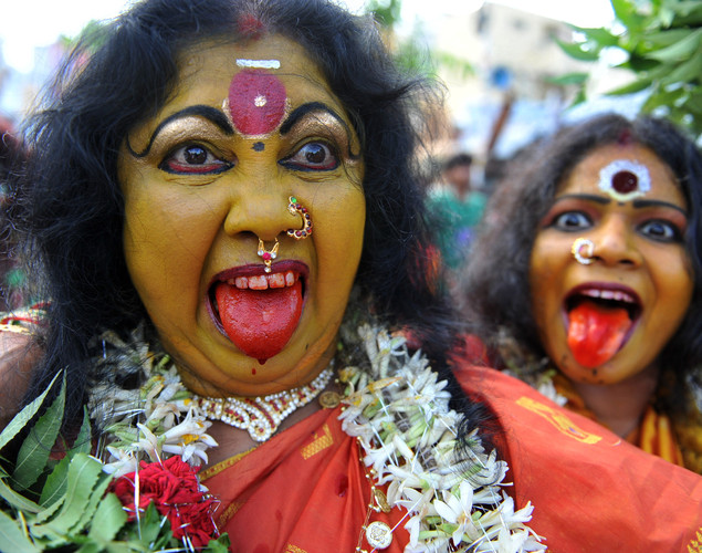Indian artists dressed as Hindu Goddess MahaKali perform in a trance during the final procession of the eleven day traditional festival of 'Bonalu'.