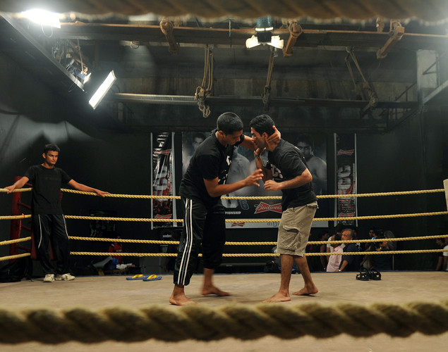 Mixed martial arts (MMA) fighter Sumeet Sawant (L) looks on as fellow fighters Gaurav Pandey (C) and Aditya Despande (R) practise moves before the start of the FCC (Full Contact Championship) 6 fight night in Mumbai.