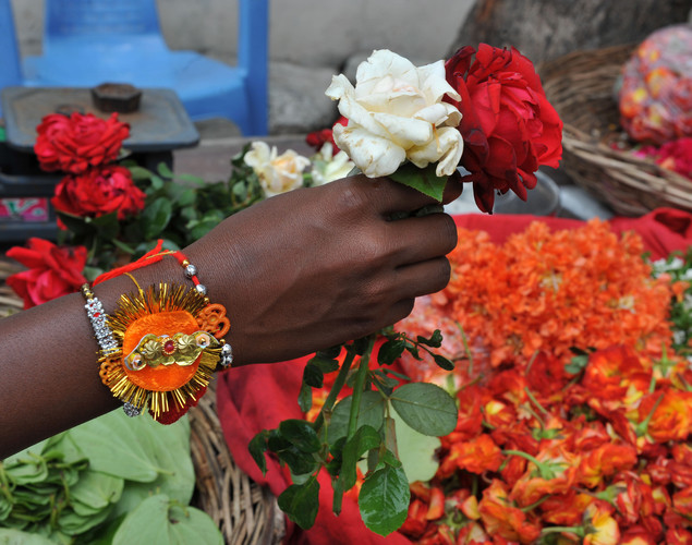 An Indian man buys roses with 'rakhi' - sacred threads - on his wrist in Hyderabad.