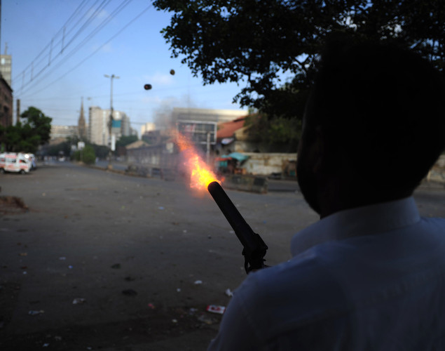 A Pakistani policeman fires a teargas shell towards demonstrators during a protest against an anti-Islam film in Karachi.