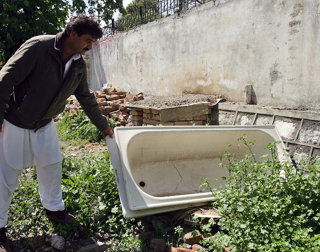 Shakeel Ahmad Yusufzai, a Pakistani contractor, pointing out a bathtub from the demolished compound of slain Al-Qaeda leader Osama bin Laden, at his residence compound in northern Abbottabad.