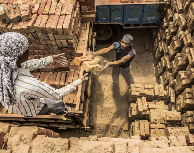 Laborers stack baked bricks onto a truck at a brick making kiln on May 23, 2012 in a village near Jaipur, India.