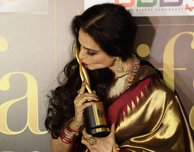 Rekha kisses her trophy after she wins the Lifetime Achievement award at the 2012 International India Film Academy Awards at the Singapore Indoor Stadium.
