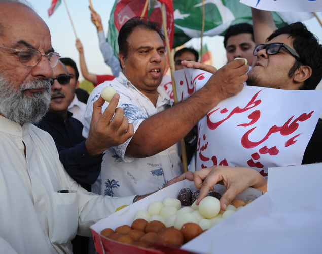 Supporters of Pakistani cricketer turned politician Imran Khan of Pakistan Tehreek-i-Insaaf (PTI - Movement for Justice) offer sweets while they celebrate following the verdict against Pakistani Prime Minister Yousuf Raza Gilani in Islamabad.