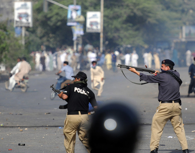 A Pakistani policeman fires towards demonstrators during a protest against an anti-Islam film in Karachi.