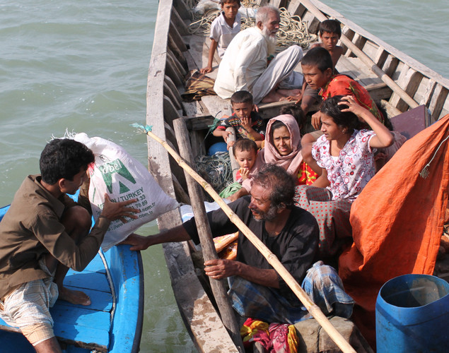 Rohingya Muslims fleeing sectarian violence receive food and water from Bangladeshis during their attempt to cross the Naf river into Bangladesh in Teknaf.