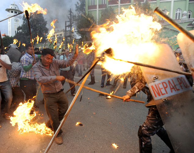 Torch-bearing Nepalese Youth Force Wing activists of the Communist Party of Nepal (UML) clash with riot police during a protest demanding the resignation of Prime Minister Baburam Bhattarai in Kathmandu.
