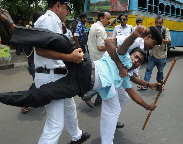 Activists of Social Unity Center of India (SUCI) scuffle with police officials as they attempt to arrest them during a law-violation protest against the recent petrol price hike in Kolkata.