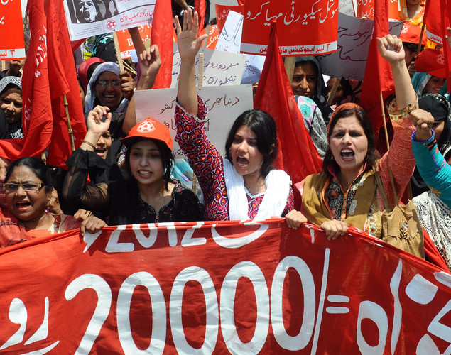 Pakistani labour union workers carry placards as they shout slogans during a May Day rally in Lahore.