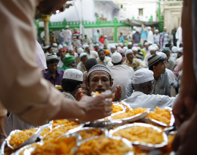 A Muslim man receives a plate of biryani rice as he and others prepare to break their fast on the first day of the holy month of Ramadan at the shrine of 13th century Sufi Muslim saint Hazrat Nizamuddin Aulia in New Delhi.