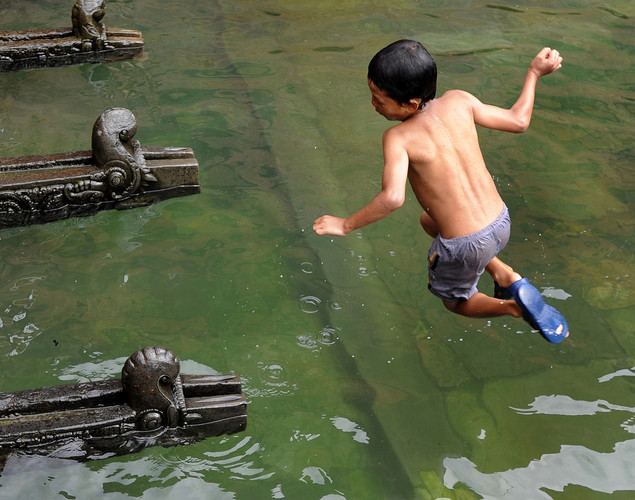 A Nepalese boy jumps into a pool of water collected from a stone spout near the Patan Durbar Square in Lalitpur, about five kilometers south-east of Kathmandu on August 30, 2012. Patan Durbar Square, a UNESCO World Heritage Site, is best known for its rich cultural heritage, particularly its tradition of arts and crafts.