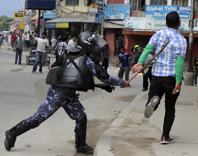 A Nepalese Youth Force Wing activist (R) of the Communist Party of Nepal (UML) is beaten by a riot policeman during a protest demanding the resignation of Prime Minister Baburam Bhattarai in Kathmandu.
