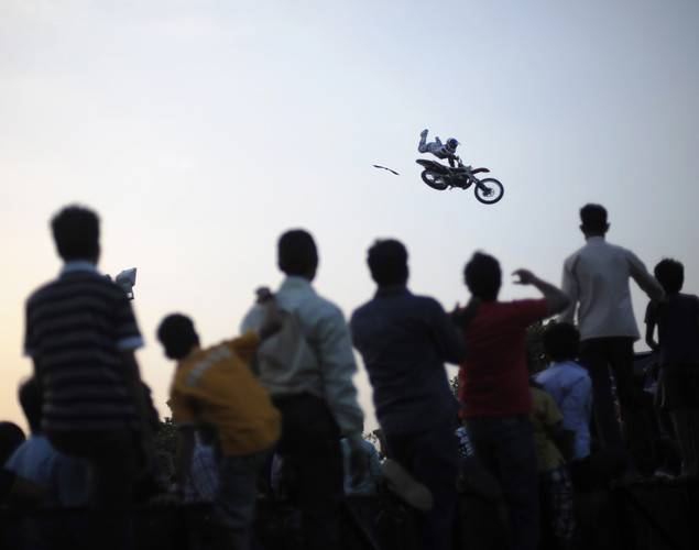 An Indian crowd watches a professional motorcyclist preform a stunt with his motorcycle after coming off a ramp during a motorcycle show near India Gate in New Delhi.