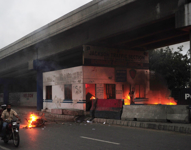 A Pakistani motorcyclist rides past a burning traffic police office during a rally against an anti-Islam movie in Karachi.