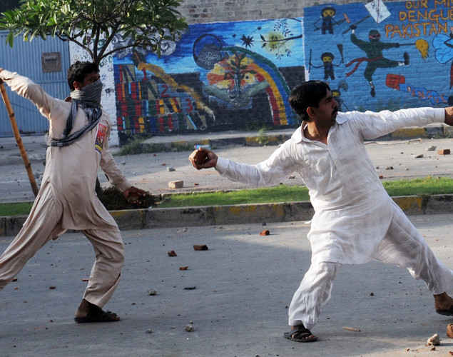 Pakistani Muslim demonstrators throw stones towards police during a protest against an anti-Islam film in Lahore.