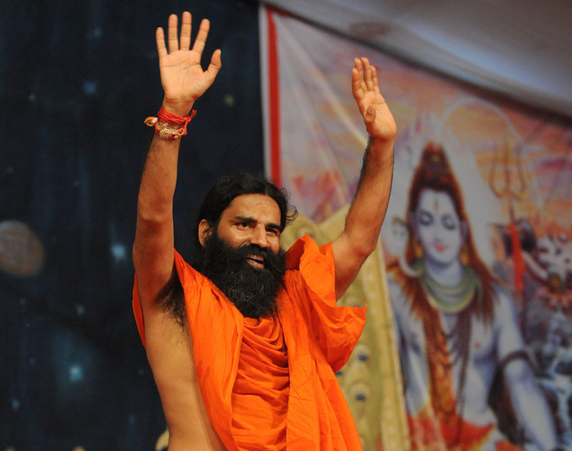 Indian yoga Guru Baba Ramdev waves from the stage after addressing devotees gathered for a religious function in Ahmedabad.