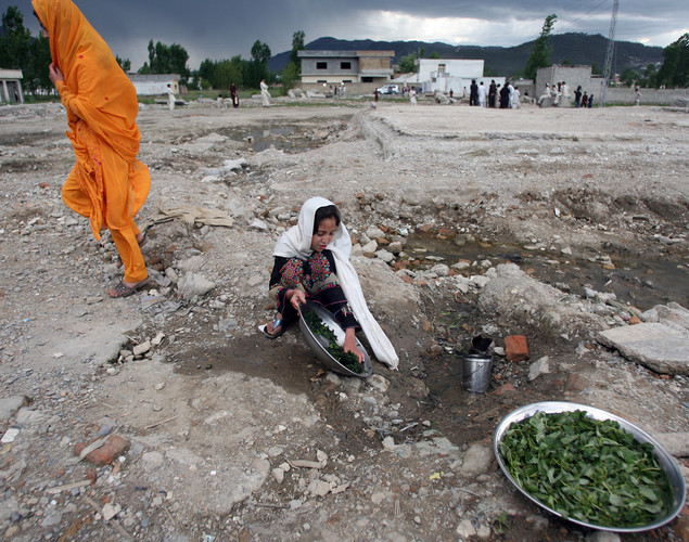 A Pakistani girl washes vegetable at the site of the demolished compound of slain Al-Qaeda leader Osama bin Laden in northern Abbottabad.