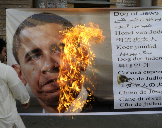 Activists of Awami Majlis-e-Amal Pakistan burn a banner of US President Barack Obama during a protest in Quetta to denounce the resumption of NATO supplies into Afghanistan.