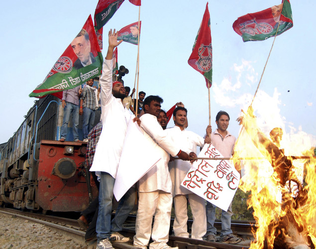 Samajwadi Party activists burn an effigy representing Indian Prime Minister Manmohan Singh after stopping a train during a strike against a petrol price hike in Allahabad.